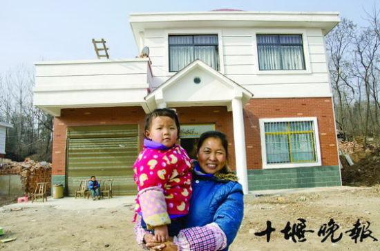 村民赵萍站在范元君为其盖的别墅前。