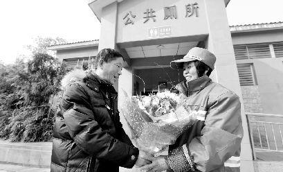 昨日,50岁的童世国将自制玫瑰花送到当公厕管理员的妻子胡泽英手中。本报记者 傅坚 摄