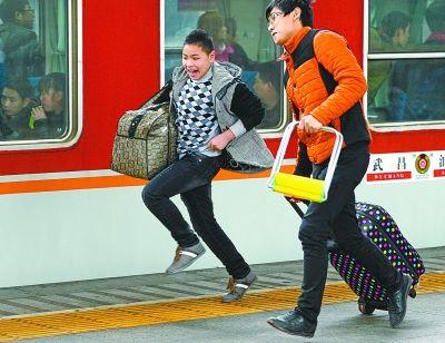 昨天,武昌火车站站台,一位男士提着旅行包快步奔向即将出发的武昌至汕头的列车。