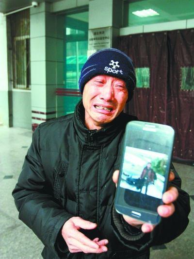 死者父亲看着儿子照片老泪纵横。 记者杨涛 摄