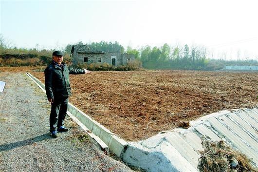 图为:张远村村支书陈前进指着一栋未拆除的旧房说,腾退宅基地不能强迫。