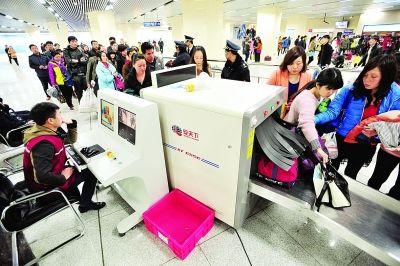 乘客们自觉的将行李箱放入安检机检查。记者詹松 摄