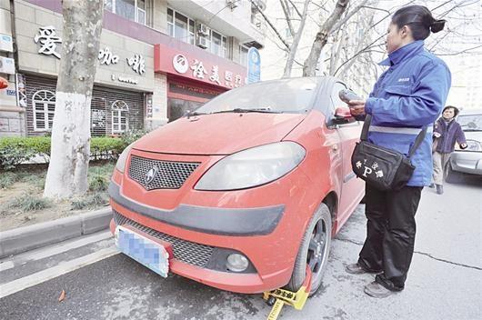 图为:街头一辆欠费车被贴上告知单并上锁 (记者万多摄)
