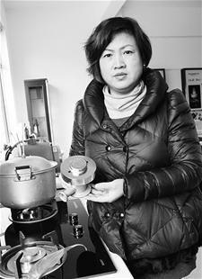 图为:何梅顺在演示她的降废燃气灶