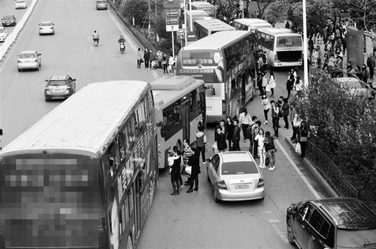 图为:一个公交站常常会有十几台公交车扎堆进站 (记者邹斌摄)