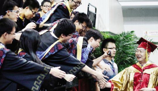 """去年6月21日,毕业生们争相与""""根叔""""握手。本报记者 原丽阳 摄"""