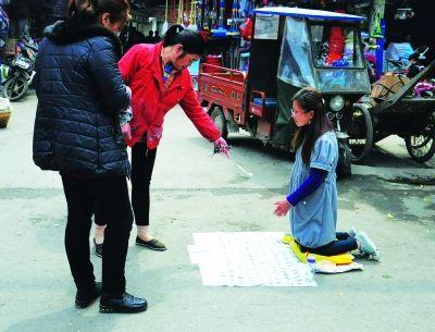 """不明真相的路人给了""""杨花""""一元钱。 见习记者杨荣峰 摄"""