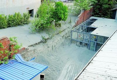 溢出的水泥将围墙冲垮。