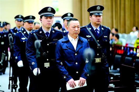 图为:刘汉等被告人被带到法庭受审。(本报报道组 摄)