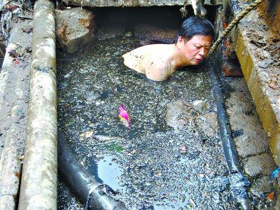 抢修哥 刘跃青 在浸泡黑色污秽物的电缆沟里抢修缆线