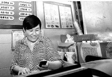 图为:收银间隙,孙女士跟丈夫、女儿互发手机短信聊天,露出开心的笑容