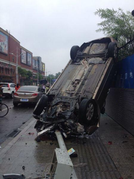 武昌发生车祸:风神撞别克后飞立墙头。(图片来源于网络)