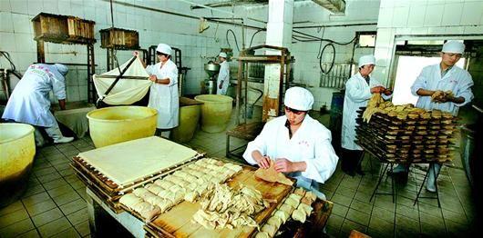 图为:图为镇上的古民居。图为:石牌镇上,工人们采用传统工艺制作香干子。