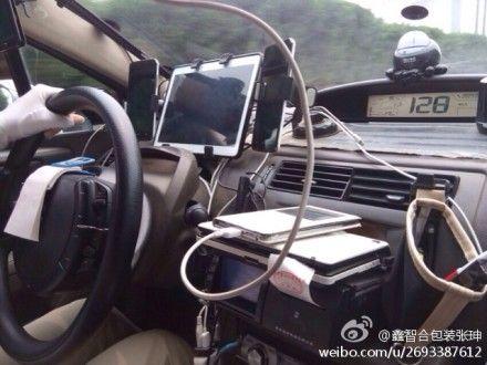 图为:驾驶台上摆了4部手机和1部ipad