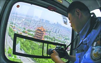 昨日,武汉特警支队最新直升机飞过黄鹤楼,执勤人员正在高空巡逻见习记者胡冬冬 摄 通讯员王威 王可 应后威