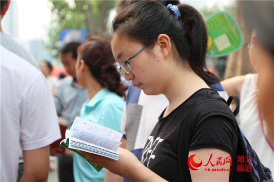 """""""临门一脚""""。早上7点50,已经有大批考生和家长聚集在武汉市十五中门口,等待进入。图为正在抓紧时间复习的考生。"""