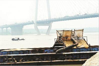 图为:白沙洲大桥下,淘金客驾驶机船在江面上穿梭