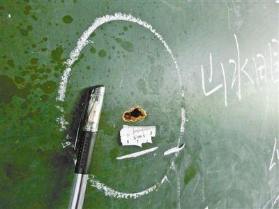 事发的教室内,黑板上残留着弹孔