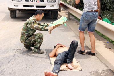 汪少文手拿一张纸板,给躺在地上的受伤男子遮阳 李国柱 摄