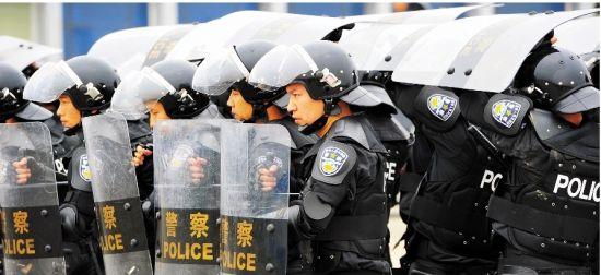图为:特警队员身着防暴盔甲演练处突队形