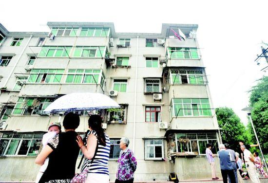 图为:居民们在事发楼房下议论纷纷