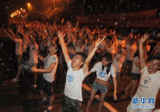 """6月21日,湖北武汉华中科技大学的毕业生在毕业狂欢上泼水庆祝。当日晚,华中科技大学2014届毕业生泼水狂欢,庆祝毕业。该校毕业泼水庆祝活动始于2006年,目前,已经成为一年一度的毕业""""重头戏""""。"""