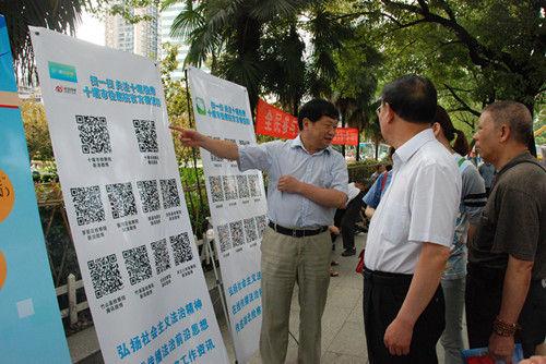 图为十堰市检察院检察长白章龙向群众推荐微博