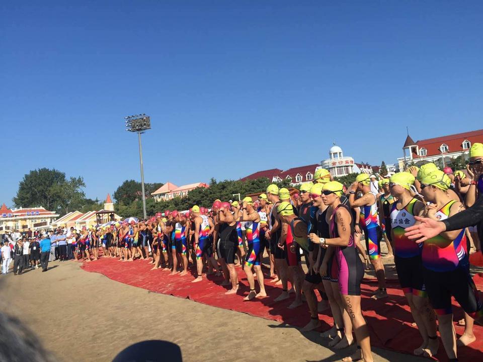 游泳项目开始前,选手们集结在沙滩上,做着最后的准备工作