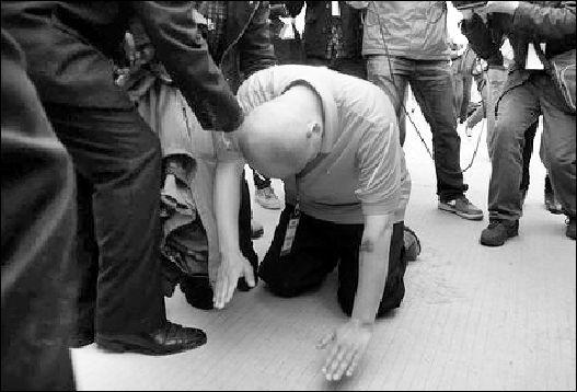 """一名民间组织人士参观完""""活熊取胆""""后,在养殖场向黑熊跪拜谢罪。 中新社图"""